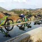 Edizione di settembre 2016 del Sardinia Divide. Bici all'abbeverata mentre il gruppo vista le domus de janas di Asuni